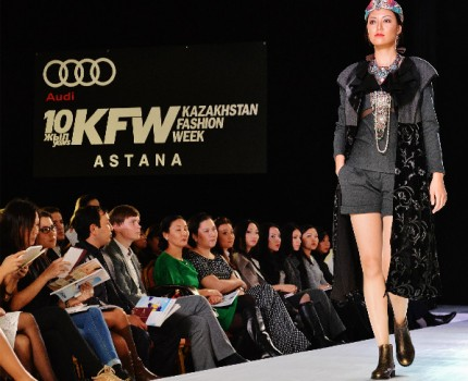 Kazakhstan Fashion Week model on runway with industry people